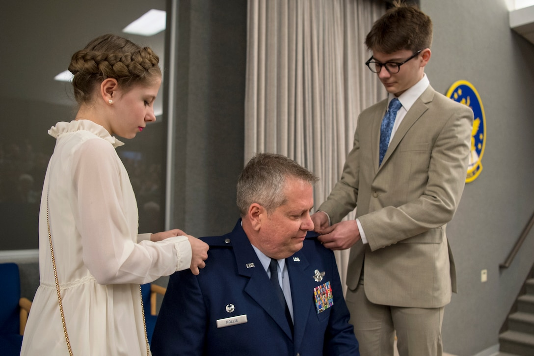 In the center, Col. Brian Hollis, 434th Operational Support Squadron commander, has his children, Isabel and Isaac, add new eagle rank insignias on his service coat during a pin-on ceremony at Grissom Air Reserve Base, Ind., April 7, 2018. Before taking command of the 434th OSS, Hollis held numerous jobs within the 434th ARW, including tanker scheduler, nuclear plans officer, assistant chief pilot tactics officer, chief of mission development, chief of plans and director of operations. (U.S. Air Force photo/Tech. Sgt. Benjamin Mota)