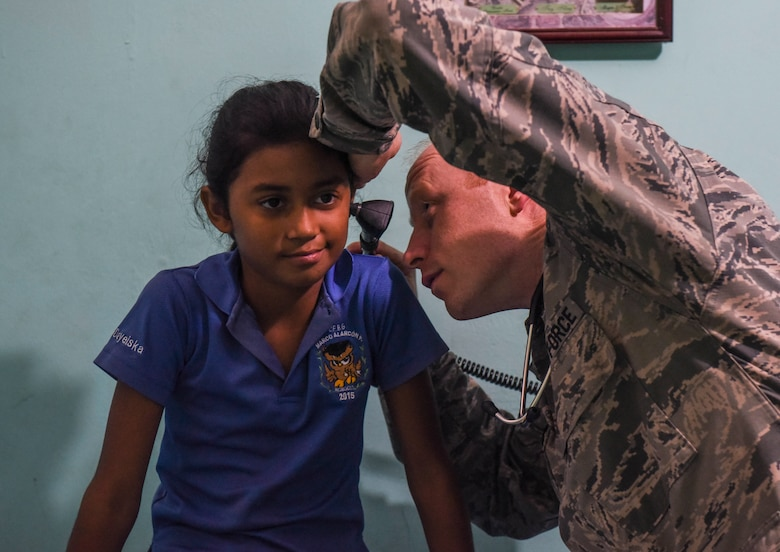 U.S. Air Force Maj. Adam Hebdon, 346th Expeditionary Medical Operations Squadron family physician, checks the ears of a local girl in Meteti, Panama, April 10, 2018. Hebdon was part of an Embedded Health Engagement Team, which gave him a unique learning experience by submerging him into local clinics. The team was participating in Exercise New Horizons 2018, which will assist communities throughout Panama by providing medical assistance and building facilities such as schools, a youth community center and a women's health ward. (U.S. Air Force photo by Senior Airman Dustin Mullen)
