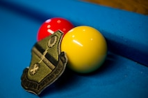 Billiard balls and a uniform patch rest on a billiard table during a spouses crud tourney, April 27, 2018, at Moody Air Force Base, Ga. The Moody spouses built the event around teamwork and comradery, giving them an opportunity to experience a long-held tradition amongst the Air Force fighter and rescue squadrons. Though the game originated in the Royal Canadian Air Force, it has since been adopted by the U.S. (U.S. Air Force photo by Airman 1st Class Erick Requadt)