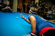 Jessica Seyfried, crud player, rolls a billiard ball at the start of a match during a spouses crud tourney, April 27, 2018, at Moody Air Force Base, Ga. The Moody spouses built the event around teamwork and comradery, giving them an opportunity to experience a long-held tradition amongst the Air Force fighter and rescue squadrons. Though the game originated in the Royal Canadian Air Force, it has since been adopted by the U.S. (U.S. Air Force photo by Airman 1st Class Erick Requadt)