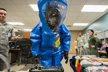 Col. Jennifer Short, center, 23 Wing commander, inspects a specimen while wearing a Level A suit, April 30, 2018, at Moody Air Force Base, Ga. Short toured the 23d Medical Group (MDG) to gain a better understanding of their overall mission, capabilities, and comprehensive duties, and was able to experience the day-to-day operations of the various units within the 23d MDG, ranging from bioenvironmental to ambulatory care. (U.S. Air Force photo by Airman 1st Class Eugene Oliver)