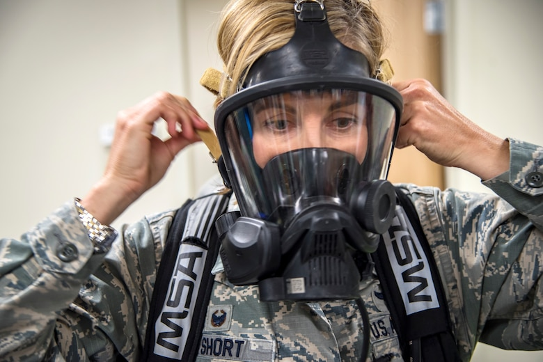 Col. Jennifer Short, 23d Wing commander, tightens a gas mask, April 30, 2018, at Moody Air Force Base, Ga. Short toured the 23d Medical Group to gain a better understanding of their overall mission, capabilities, and comprehensive duties, and was able to experience the day-to-day operations of the various units within the 23d MDG, ranging from bioenvironmental to ambulatory care. (U.S. Air Force photo by Airman 1st Class Eugene Oliver)