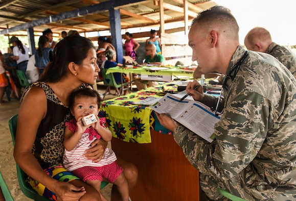 U.S. Air Force Capt. Charles Hutchings, 346th Expeditionary Medical Operations Squadron pediatrician, explains info to a local woman near.