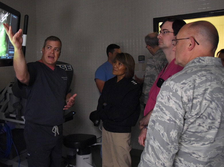 Greg Street, Intuitive Surgical instructor, left, briefs U.S. Navy Vice Adm. Raquel Bono, Defense Health Agency director, on the capabilities of robotics surgery at the Clinical Research Lab during a site visit at Keesler Air Force Base, Mississippi, April 27, 2018. The purpose of the visit was to get oriented with base operations and the Keesler Medical Center. The visit also included an office call with 2nd Air Force leadership and tours of Radiology Oncology and the newly renovated 81st Dental Squadron clinic. (U.S. Air Force photo by Kemberly Groue)