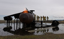 Oregon Air National Guard Airmen from Kingsley Field and civil engineer officers from various locations across the U.S. walk into an aircraft's interior during a live fire training at Fairchild Air Force Base, Washington, April 18, 2018. The rigorous hands-on training consists of aircraft and structure live-fire scenarios. This gave both groups training in all aspects of firefighting such as emergency mitigation, prevention, communications, health, safety and mutual aid support to their local communities. (U.S. Air Force photo/Airman 1st Class Jesenia Landaverde )