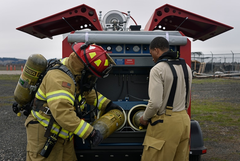 Senior Airman Jonathan Jones, 92nd Civil Engineer Squadron Fire Department firefighter, refills a self-contained breathing apparatus during a simulated aircraft live fire at Fairchild Air Force Base, Washington, April 18, 2018. The 92nd CES Fire Department coordinated and facilitated the classroom and hands-on portions of this joint service fire training and fire marshal training course. (U.S. Air Force photo/Airman 1st Class Jesenia Landaverde)