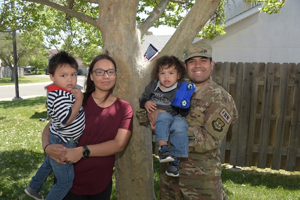 Savannah Ruiz (Left) and her husband, Senior Airman Ruben Ruiz (Right), 921st Contingency Response Squadron aerial porter, pose for a photo with their children outside their home at Travis Air Force Base, Calif., April 26, 2018. The couple attended the Financial Peace Military course and used what they learned to pay off three credit cards, reducing their debt by $5,000. (U.S. Air Force photo by Tech. Sgt. James Hodgman)