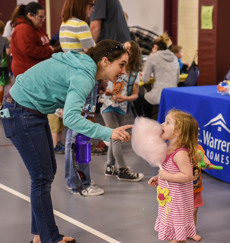 A mom gives her child cotton candy during the Month of the Military Child Spring Bash April 27, 2018, on F.E. Warren Air Force Base, Wyo. Cotton candy was just one of the many treats provided for the children by the youth center staff. The 90th Force Support Squadron held this spring bash to celebrate the children of military members and what they experience.  (U.S. Air Force photo by Airman 1st Class Braydon Williams)