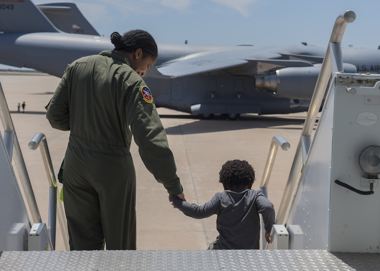 U.S. Air Force Staff Sgt. Liahna Childs, an instructor boom assigned to the 54th Air Refueling Squadron, and her son exit a KC-135 Stratotanker, April 26, 2018, at Altus Air Force Base, Okla.