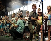 A photo of children dancing on stage during a performance by the Lt. Dan Band, April 26, 2018, at Mountain Home Air Force Base, Idaho. Approximately 800 military members, veterans, family and friends attended the Lt. Dan Band concert. (U.S Air Force Photo by Airman 1st Class Hailey Bivens)