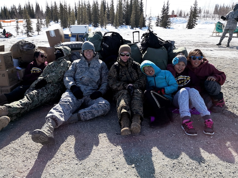 Senior Airman Elliott Bull (center left) and local children from Shungnak, Alaska, hunker down for shelter amidst strong winds while waiting for a helicopter to arrive