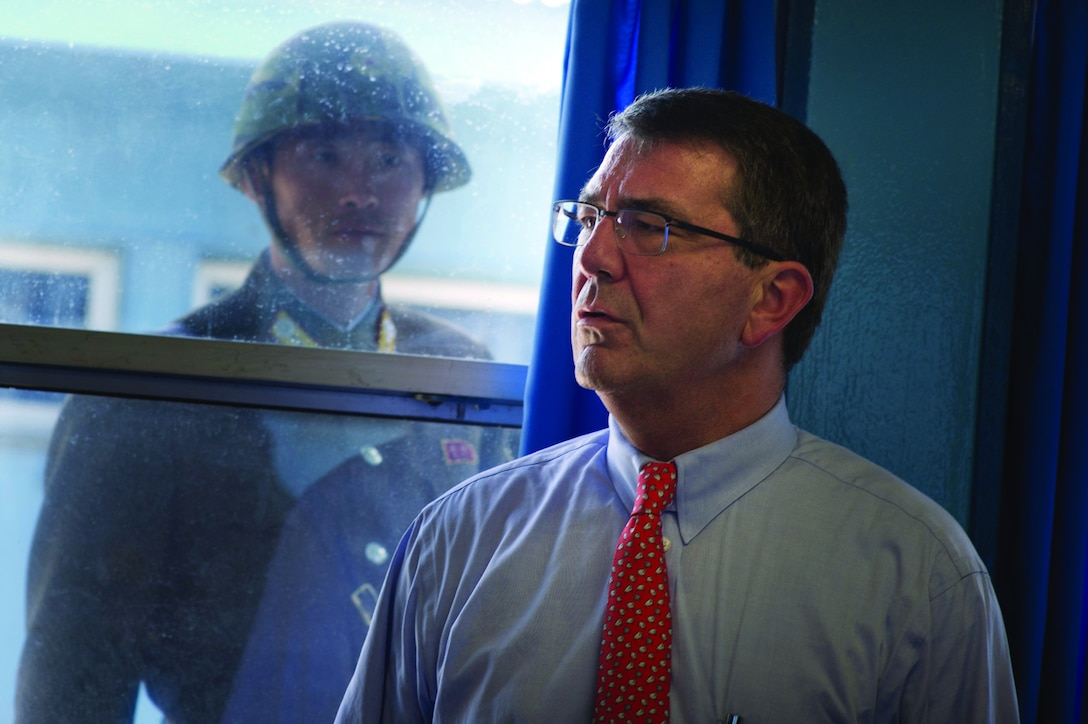 U.S. Deputy Secretary of Defense Ashton B. Carter, right, tours the Military Armistice Commission Building in Panmunjom, South Korea, in the demilitarized zone separating North and South Korea July 26, 2012, as a North Korean soldier watches. Carter wrapped up a 10-day Asia-Pacific trip visiting partners in Hawaii, Guam, Japan, Thailand, India and South Korea. (DoD photo by Mass Communication Specialist 1st Class Chad J. McNeeley, U.S. Navy/Released)