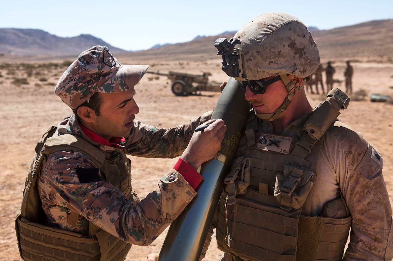 A Jordanian marine writes the name of U.S. Marine Corps Sgt. Micah N. Pauly on a 105 mm Howitzer round.