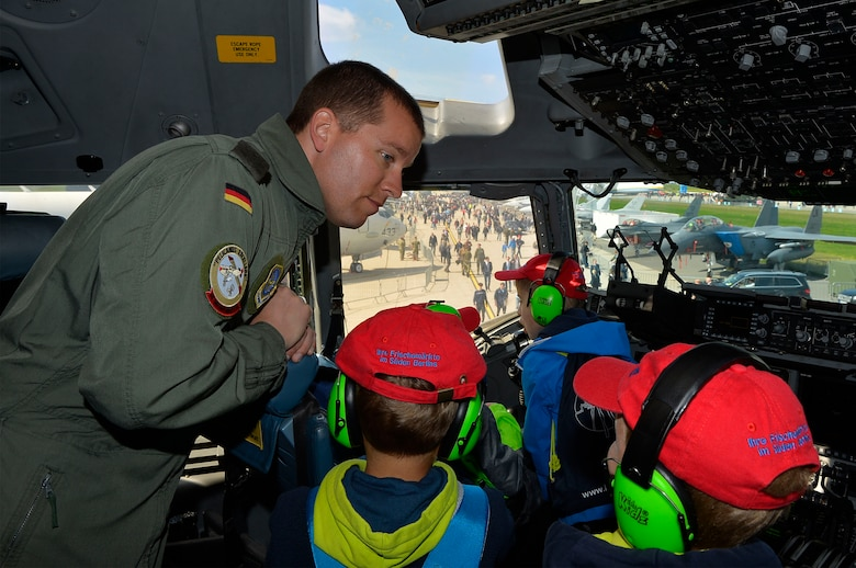 German air force Maj. Rico Persy, a foreign exchange pilot stationed at Joint Base Charleston, S.C., shows German school children the features of a U.S. Air Force C-17 Globemaster III in Berlin, Germany, April 27, 2018. The Military Personnel Exchange program allows U.S. and foreign pilots to train train closely with their allies and familiarize themselves with other aircraft. (U.S. Air Force photo by Senior Airman Joshua Magbanua)