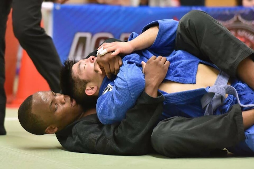 A competitor puts a choke hold on another during a jiujitsu match.
