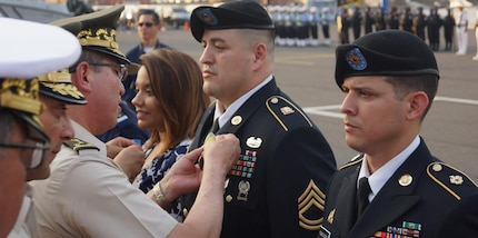 A Guatemalan general officer pins a medal on a U.S. Soldier.