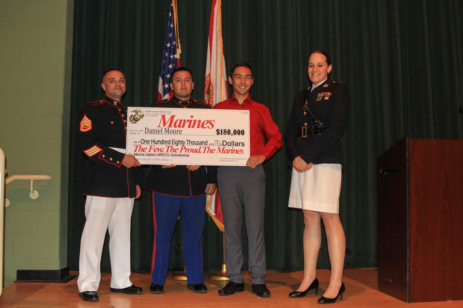 Capt. Jennifer Mozzetta, executive officer, Recruiting Station Tampa, SSgt. Brenton Spriggs (left), station commander, Recruiting Substation Leesburg and Sgt. Gabriel Osorio, canvassing recruiter, present Daniel Mmoore, a senior at Lake Minneola High School, Minneola, Fl., the Naval Reserve Officer Training Corps Marine Option Scholarship during an awards ceremony May 2, 2018. Moore will be granted the opportunity to serve his country as a Marine Corps officer upon completion of his degree. (Official Marine Corps photo by Sgt. Calvin Shamoon/ Released)