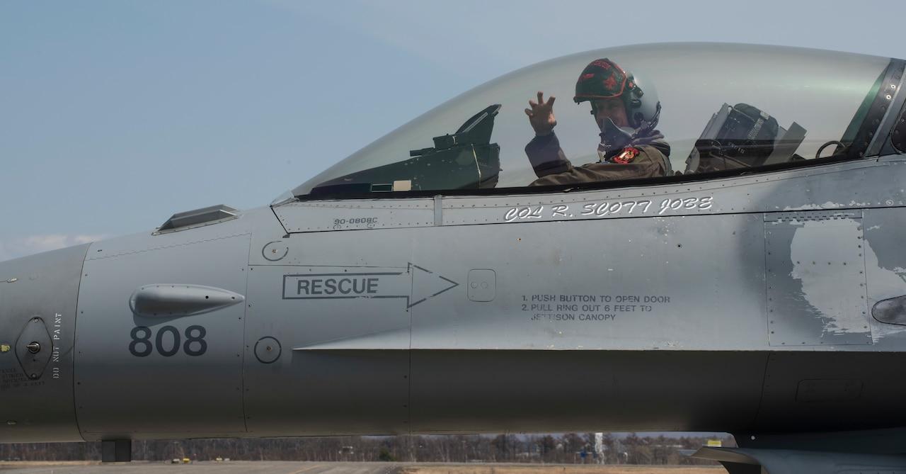 U.S. airman sits in F-16 cockpit.