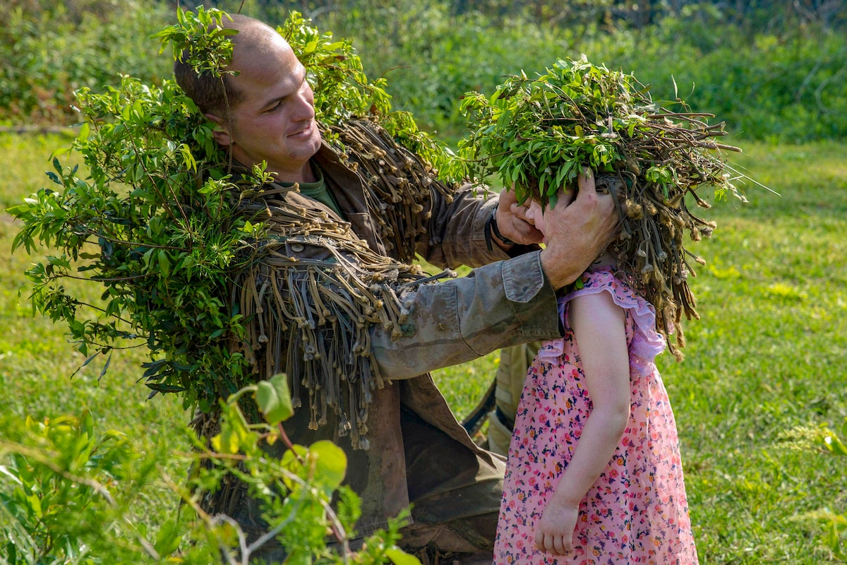 A kneeling Marine puts a cap of foliage on a child's head in a green field.