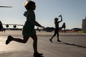 Two children run near aircraft.