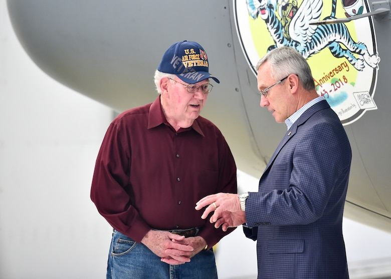 Lt. Col. (ret.) John Wingerter, a former pilot with the 757th Airlift Squadron here, talks with Youngstown State University President Jim Tressel, in front of C-130H Hercules nose art depicting the 757th AS Blue Tiger mascot in honor of the 75th anniversary of the 757th AS after an unveiling ceremony here, May 3, 2018.