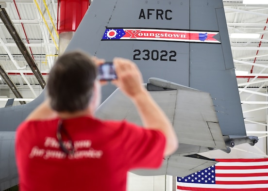 Dave Deibol, a member of the Youngstown Air Reserve Base-Community Council and honorary 910th Operations Group commander, takes a photo of the new Youngtown Air Reserve Station tail flash during an unveiling ceremony here, May 3, 2018.