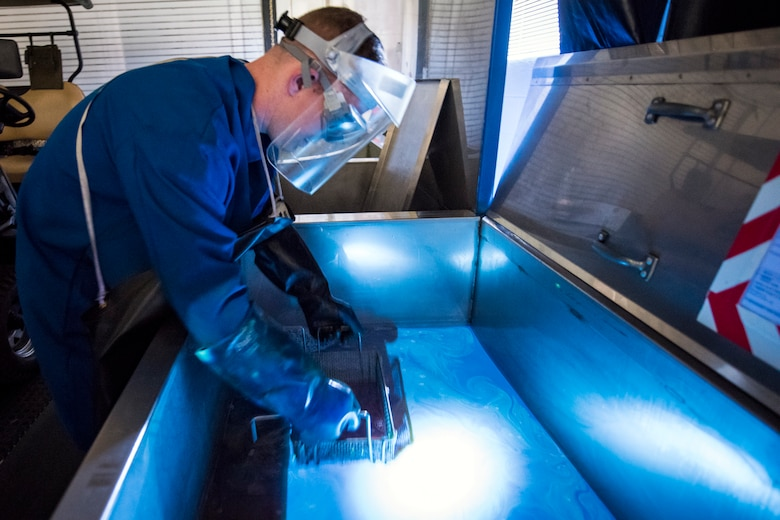 Senior Airman Matthew Horne, 23d Maintenance Squadron non-destructive inspection (NDI) specialist, lifts an aircraft part out of a pool of florescent dye, May 2, 2018, at Moody Air Force Base, Ga. NDI technicians use various methods to complete these inspections such as X-ray, florescent dye penetrant, oil analysis and ultrasonic scanning to examine and inspect numerous aircraft parts and components to ensure that they are in usable condition. (U.S. Air Force photo by Airman 1st Class Eugene Oliver)