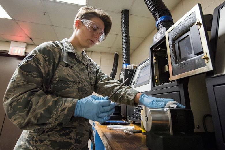 Senior Airman Louisa Doyle, 23d Maintenance Squadron non-destructive inspection (NDI) specialist, examines a steel rod, May 2, 2018, at Moody Air Force Base, Ga. NDI technicians use various methods to complete these inspections such as X-ray, florescent dye penetrant, oil analysis and ultrasonic scanning to examine and inspect numerous aircraft parts and components to ensure that they are in usable condition. (U.S. Air Force photo by Airman 1st Class Eugene Oliver)