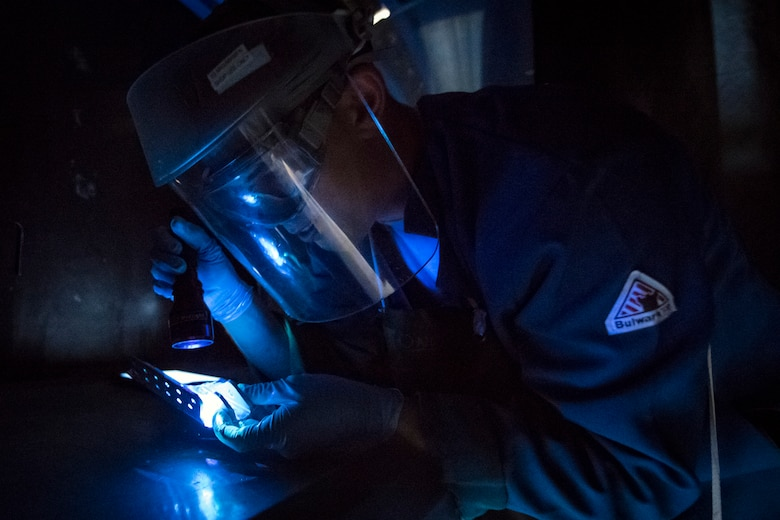 Senior Airman Matthew Horne, 23d Maintenance Squadron non-destructive inspection (NDI) specialist, examines an aircraft part, May 2, 2018, at Moody Air Force Base, Ga. NDI technicians use various methods to complete these inspections such as X-ray, florescent dye penetrant, oil analysis and ultrasonic scanning to examine and inspect numerous aircraft parts and components to ensure that they are in usable condition. (U.S. Air Force photo by Airman 1st Class Eugene Oliver)