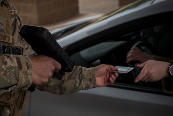 An Airman, with the 27th Special Operations Security Forces Squadron, checks an ID May 2nd, at Cannon Air Force Base, New Mexico. One of the duties while working the gate involves checking the ID of everyone who wants on base. (U.S. Air Force Photo by A1C Gage Adison Daniel/Released)