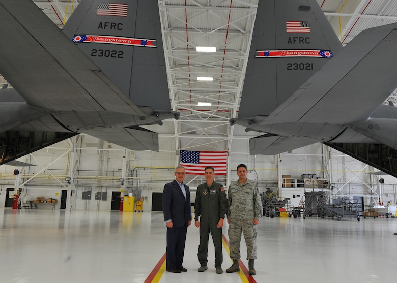 Youngstown State University President and Honorary 910th Airlift Wing Commander Jim Tressel, 910th AW Commander Col. Dan Sarachene and 910th AW Public Affairs Office Superintendent Master Sgt. Bob Barko Jr. (left to right), pose for a photo under two C-130H Hercules tails with the new tail flash design during an unveiling ceremony here May 3, 2018.
