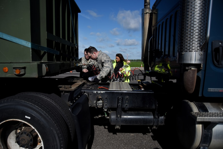 Staff Sgt. Alexander Lawrence, 100th Logistics Readiness Squadron training and validation office examiner, center, performs a vehicle check during a course inspection at Royal Air Force Mildenhall, England, April 26, 2018. The CDL course is part of an Air Force-wide initiative, with RAF Lakenheath and RAF Mildenhall set to be the first bases to implement the program in the U.S. Air Forces in Europe. (U.S. Air Force photo/Senior Airman Abby L. Finkel)