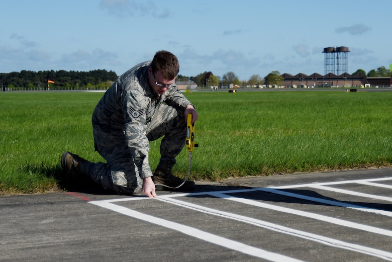 Staff Sgt. Andrew Rodman, 48th Logistics Readiness Squadron training and validation office examiner, measures the lines of a vehicle training course during an inspection at Royal Air Force Mildenhall, England, April 26, 2018. The inspection verified procedures and the course layout to be used for a commercial driver's licensure program.  (U.S. Air Force photo/Senior Airman Abby L. Finkel)