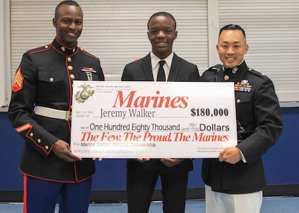 Major Richard Lee (right), commanding officer, Recruiting Station Tampa and Sgt. Jeremy Woody (left), canvassing recruiter, Recruiting Substation Temple Terrace, present Jeremy Walker, a senior at King High School, Tampa, Fl., the Naval Reserve Officer Training Corps Marine Option Scholarship during an awards ceremony April 12, 2018. Walker will be granted the opportunity to serve his country as a Marine Corps officer upon completion of his degree. (Official Marine Corps photo by Sgt. Calvin Shamoon/ Released)