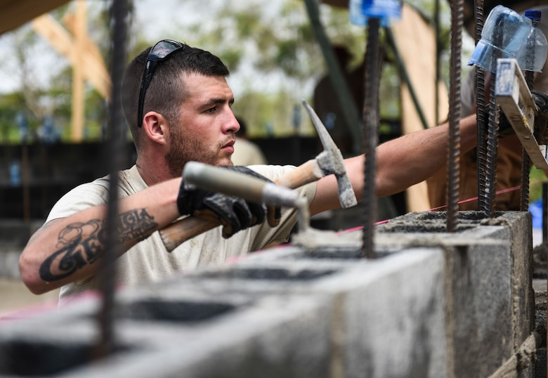 Senior Airman Dan Bentz, 346th Air Expeditionary Group Rapid Engineer Deployable Heavy Operational Repair Squadron Engineer member who is deployed from Nellis Air Force Base, Nev., hammers a concrete block into place April 27, 2018, at a construction site in Meteti, Panama. Bentz is participating in Exercise New Horizons 2018, which will assist communities throughout Panama by providing medical assistance and building facilities such as schools, a youth community center and a women's health ward. (U.S. Air Force photo by Senior Airman Dustin Mullen)