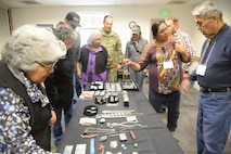 Eldrick Seoutewa (at right), an artist from Zuni Pueblo, New Mexico, demonstrates his jewelry for the attendees of the  Annual American Indian Meeting held at the Utah Test and Training Range April 20, 2018, in which Hill Air Force Base was a co-host. The meeting was held for government-to-government conversations, tours of UTTR, and official tribal co-host presentations. (U.S. Air Force photo by Cynthia Griggs)