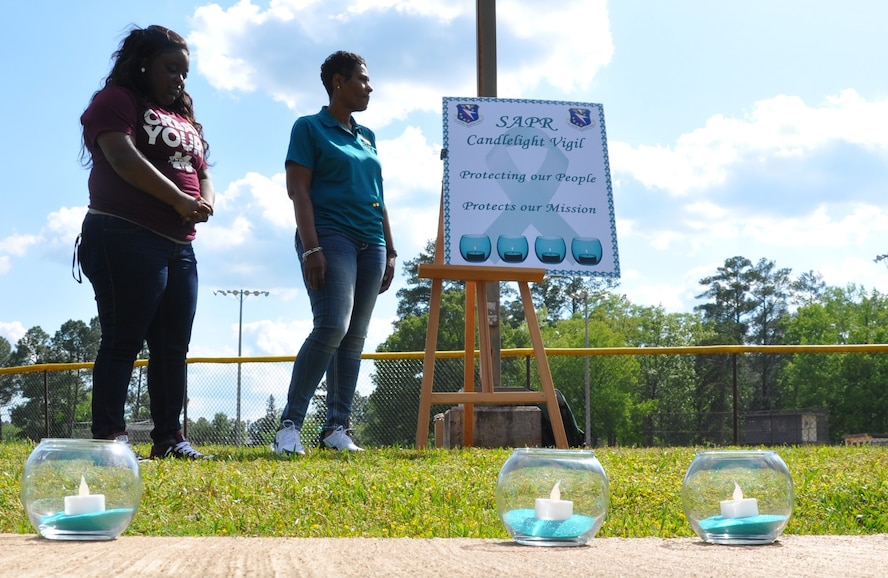 Dr. Marcia Stewart, 14th Flying Training Wing Sexual Assault Prevention and Response program manager, and a volunteer from Mississippi State University hold a moment of silence for the victims of sexual assault April 27, 2018, on Columbus Air Force Base, Mississippi. The SAPR team worked with MSU and other colleges to help educate and raise awareness about sexual assault prevention and what to do if someone has be affected. (U.S. Air Force photo by Sonic Johnson)