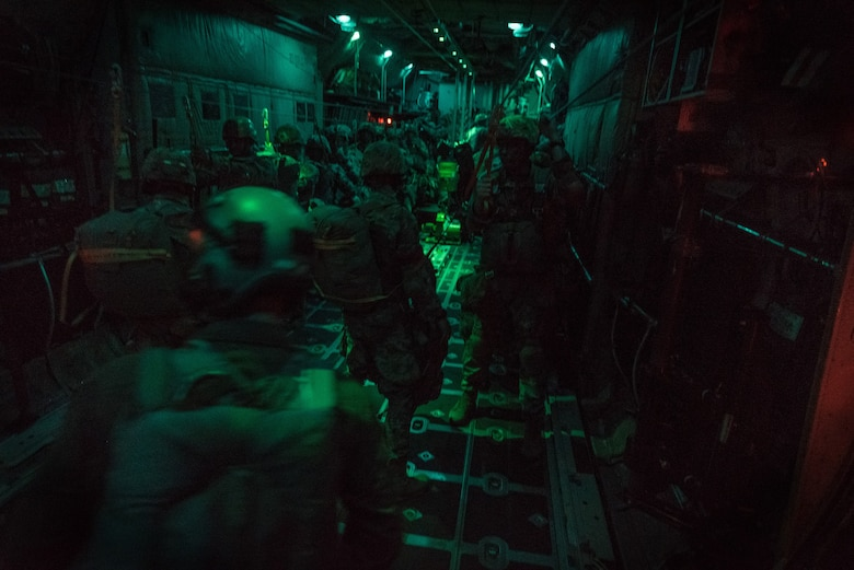 Paratroopers with 1st Battalion (Airborne), 143rd Infantry Regiment, Texas Army National Guard, prepare to initiate an airborne assault by jumping from a C-130H Hercules over Denison, Texas, April 20, 2018.
