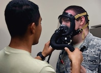 Senior Airman Rolando Chavez, 14th bioenvironmental journeyman, fits a gas mask on Senior Airman Kevin Morgan, 14th bioenvironmental journeyman May 2, 2018, on Columbus Air Force Base, Mississippi. The 14th Medical Group promotes wellness to ensure the highest state of wartime readiness combat capability for over 58,000 sorties accomplished by the 14th Flying Training Wing. (U.S. Air Force photo by Airman 1st Class Keith Holcomb)
