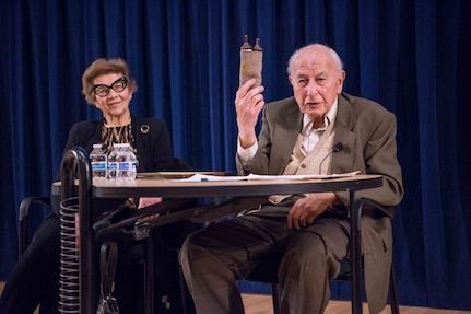 Fred Flatow shows the audience a Torah Scroll he found as a child in a burned-down synagogue. Flatow gave a detailed account of his memories as a Jewish boy growing up in East Prussia at the time of the Nazi regime during the Naval Surface Warfare Center, Carderock Division Holocaust Remembrance event in West Bethesda, Md., on April, 24, 2018. Flatow was joined by his wife, Ursel. (U.S. Navy photo by Jake Cirksena/Released)