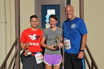 Col. Brent Merritt, 94th Airlift Wing commander; Senior Airman David Flynn, 94th Aeromedical Staging Squadron; and Capt. Rebecca Nistler, 94th Operations Group, pose for a photo after the Falcon 5k Sept. 13, 2015, at Dobbins Air Reserve Base, Ga. Flynn and Nistler were the first male and female finishers of the fun run sponsored by the Dobbins Top 3. (U.S. Air Force photo/Staff Sgt. Kelly Goonan)