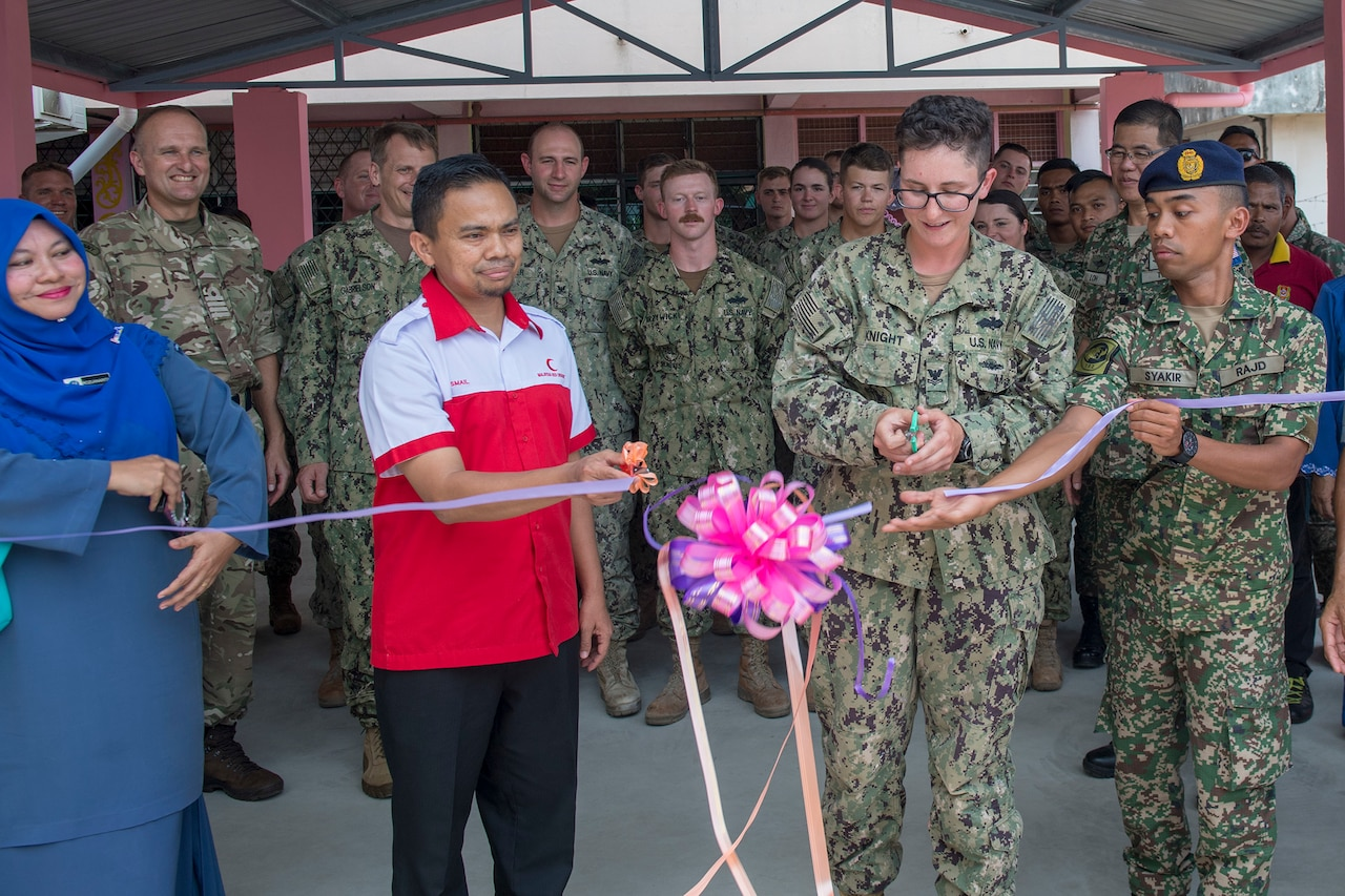 Navy Petty Officer 2nd Class Courtney Knight cuts the ribbon during an engineering project conclusion ceremony at Sek Keb TMN Taman Primary School in support of exercise Pacific Partnership 2018 in Tawau, Malaysia.