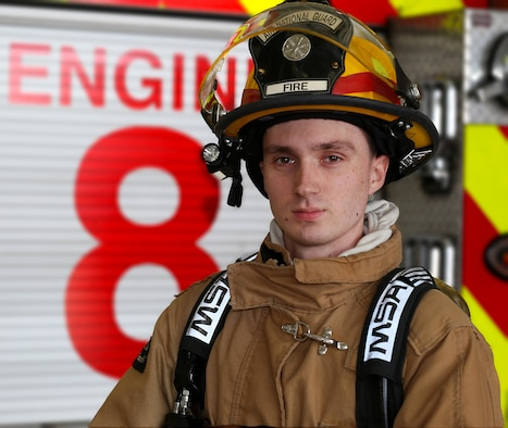 Senior Airman Alex J. Lane, an aircraft rescue firefighter assigned to the 157th Air Refueling Wing Fire Department, poses for a portrait behind a fire engine on May 4, 2018 at Pease Air National Guard Base, N.H. Lane has been a member of the Wing since 2014. (N.H. Air National Guard photo by Staff Sgt. Kayla White)