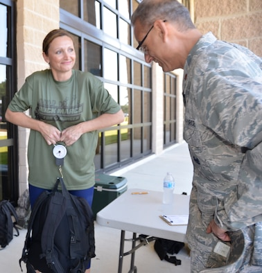 Senior Master Sgt. Tricia DeLuna, 1st Air Force (Air Forces Northern) Manpower & Personnel Directorate, weighs the backpack of  Maj. Peter Shinn, 601st air Operations Center executive officer, prior to the start of the second annual 5K Ruck March For Hunger May 4 here. Military and civilian members of 1st Air Force and the 601st Air Operations Center and their family members participated to raise awareness about hunger along with food donations for community food pantries and agencies in the Panama City area.  Nearly 100 people donned 30+ lb. ruck sacks, back packs or donated food to support the food drive which raised 1,911 lbs. The drive began last year when a 1st Air Force Airman saw a statistic stating that numerous students in Bay County were going to school hungry.