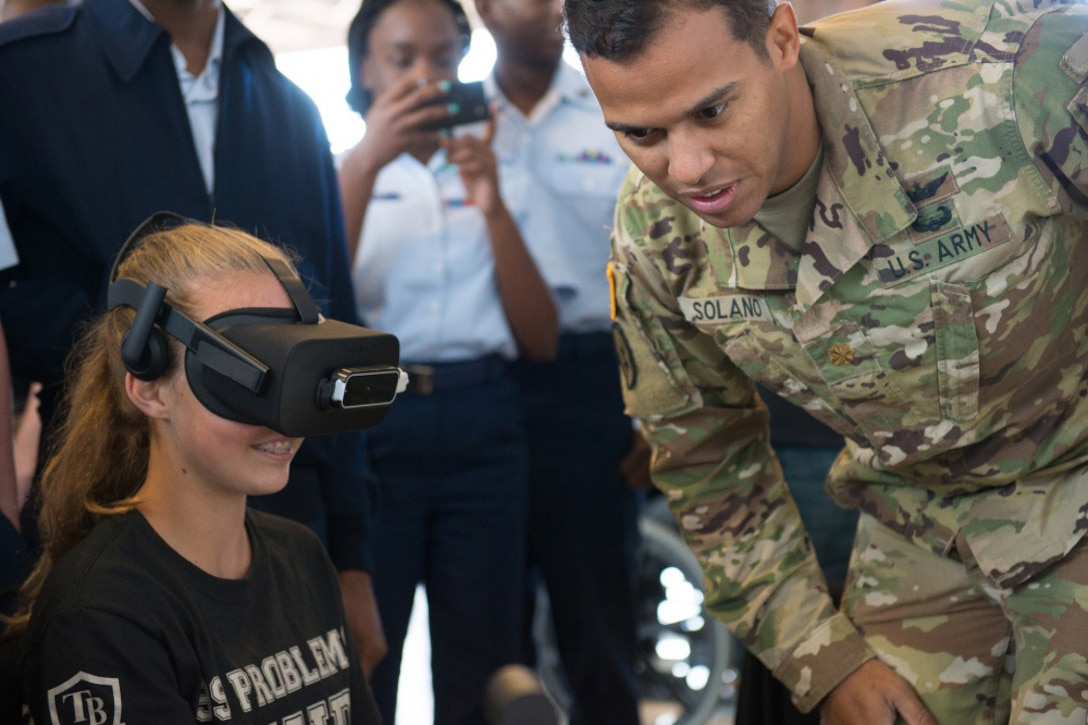 Army Maj. Robert Solano, with U.S. Special Operations Command Special Operations Forces Acquisition, Technology and Logistics directorate, demonstrates an MH-47 Chinook helicopter virtual trainer during Science, Technology, Engineering and Mathematics Day at MacDill Air Force Base in Tampa, Fla.