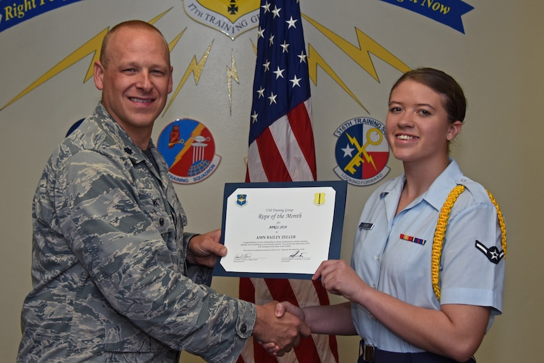 U.S. Air Force Lt. Col. Steven Watts, 17th Training Group deputy commander, presents the 17th TRG Rope of the Month award to Airman Bailey Zeller, 315th Training Squadron trainee, at Brandenburg Hall on Goodfellow Air Force Base, Texas, May 4, 2018. The 315th TRS's vision is to develop combat-ready intelligence, surveillance and reconnaissance professionals and promote an innovative squadron culture and identity unmatched across the U.S. Air Force. (U.S. Air Force photo by Airman 1st Class Zachary Chapman/Released)
