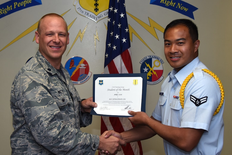 U.S. Air Force Lt. Col. Steven Watts, 17th Training Group deputy commander, presents the 312th Training Squadron Student of the Month award to Airman 1st Class Jonathan Liu, 312th TRS trainee, at Brandenburg Hall on Goodfellow Air Force Base, Texas, May 4, 2018. The 312th TRS's mission is to provide Department of Defense and international customers with mission ready fire protection and special instruments graduates and provide mission support for the Air Force Technical Applications Center. (U.S. Air Force photo by Airman 1st Class Zachary Chapman/Released)