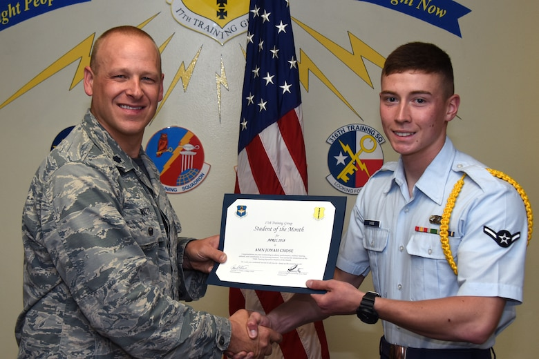 U.S. Air Force Lt. Col. Steven Watts, 17th Training Group deputy commander, presents the 316th Training Squadron Student of the Month award to Airman Jonah Chose, 316th TRS trainee, at Brandenburg Hall on Goodfellow Air Force Base, Texas, May 4, 2018. The 316th TRS's mission is to conduct U.S. Air Force, U.S. Army, U.S. Marine Corps, U.S. Navy and U.S. Coast Guard cryptologic, human intelligence and military training. (U.S. Air Force photo by Airman 1st Class Zachary Chapman/Released)