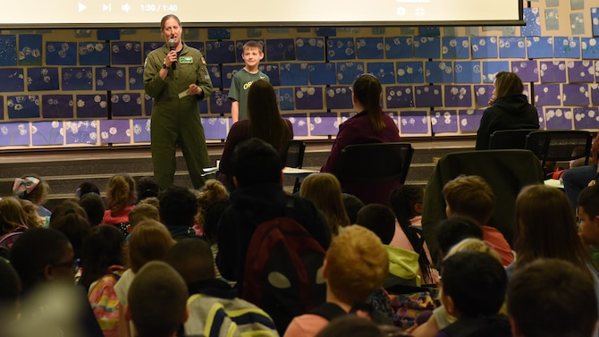 During Carter Lake Elementary School's Month of the Military Child ceremony April 27, 2018 at Joint Base Lewis-McChord, Wash., Lt. Col. Beth Lane, 62nd Airlift Wing director of staff, left, encourages participation from kindergarten through fifth graders as her son, Josh Lane (8) rewarded enthusiastic responders with prizes.