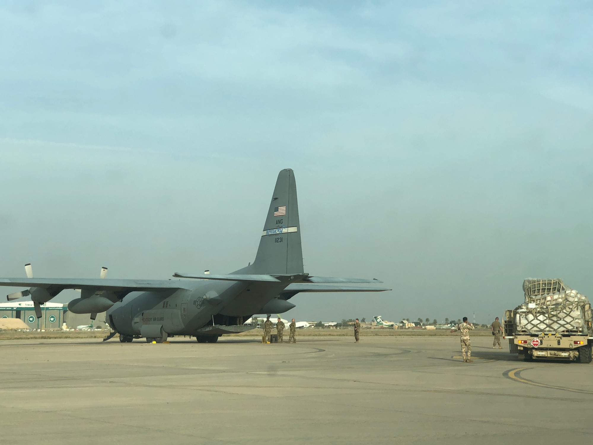 Iraqi Air Force aerial port technicians back up a K-Loader after removing cargo off a C-130 Hercules from the Kentucky Air National Guard, at Al Muthana Air Base, April 5, 2018. The Iraqi aerial port technicians, along with 370th Air Expeditionary Advisory Group air advisor observers, who are part of the Coalition Aviation Advisory and Training Team, worked together to off-load cargo and load three C-130J Super Hercules engines on to U.S. Air Force aircraft, being sent back to the manufacturer for maintenance. (Courtesy Photo)